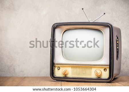 Retro old outdated TV receiver from circa 50s on wooden table front textured concrete wall background. Vintage style filtered photo
