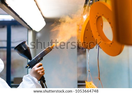 Powder coating of metal parts. A woman in a protective suit sprays powder paint from a gun on metal products #1053664748