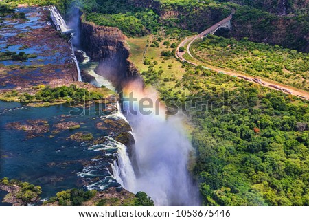 Rainbow over Victoria Falls in Zimbabwe, sunny day in Africa Royalty-Free Stock Photo #1053675446