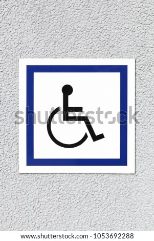 Handicap or wheelchair person symbol on a wall #1053692288