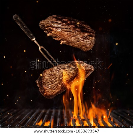Flying beef steaks over flaming grill grid, isolated on black background. Barbecue and cooking #1053693347