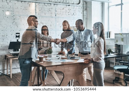 Another project done. Young modern men in smart casual wear shaking hands while standing with their colleagues behind the glass wall in the board room #1053695444