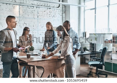 Team at work. Group of young modern people in smart casual wear discussing business while standing behind the glass wall in the creative office            #1053695459