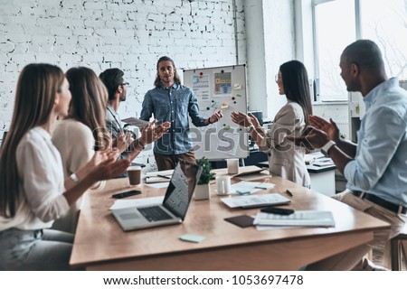 It was very interesting. Modern young business people clapping and smiling while spending time in the board room #1053697478