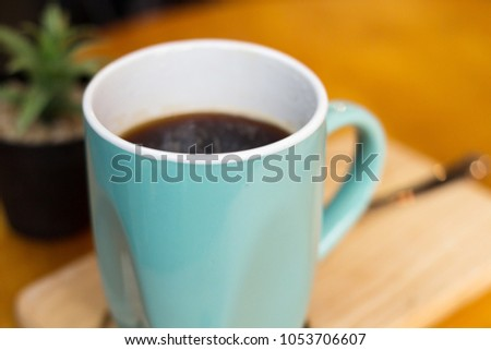 A green ceramic cup with black coffee  #1053706607