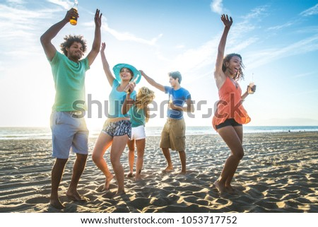 Multicultural group of friends partying on the beach - Young people celebrating during summer vacation, summertime and holidays concepts #1053717752