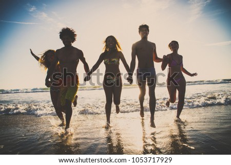 Multi-ethnic group of friends running on the beach - Young people having fun in the sea during summer holidays #1053717929