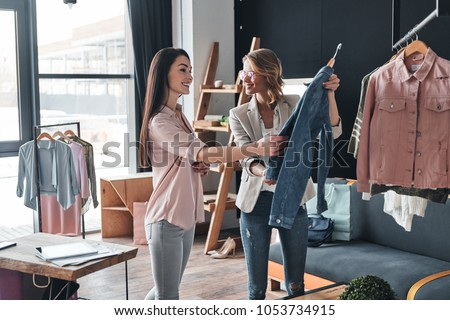 What do you think about this one? Beautiful young woman helping to choose clothes to her customer while working in the fashion boutique Royalty-Free Stock Photo #1053734915