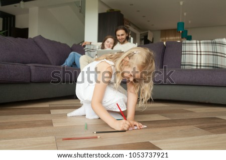 Cute daughter drawing with colored pencil sitting on warm house floor while parents using laptop on sofa, creative little kid girl playing alone, family leisure activities and hobbies at home concept #1053737921