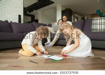 Children boy and girl having fun drawing on warm house floor while parents using laptop, kids siblings son daughter playing together, happy family leisure home activity or underfloor heating concept #1053737930