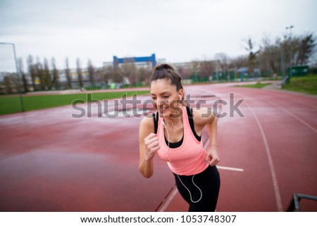 Portrait of attractive young happy fitness girl jogging while listening to music outside on running track. #1053748307