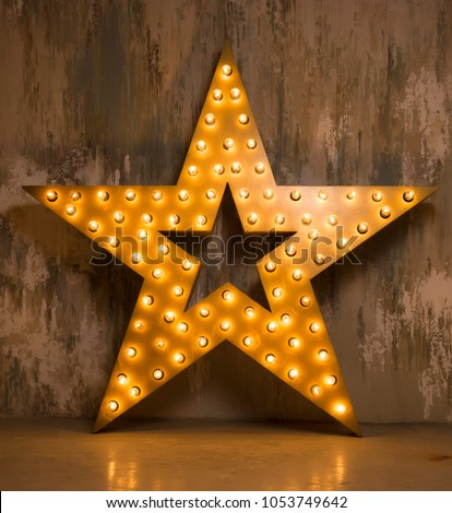 Large wooden star with a large number of lights are lit. Beautiful decor, design. Loft style Studio. Dark concrete background. Christmas, holiday, honorary star. Five stars 5 stars #1053749642