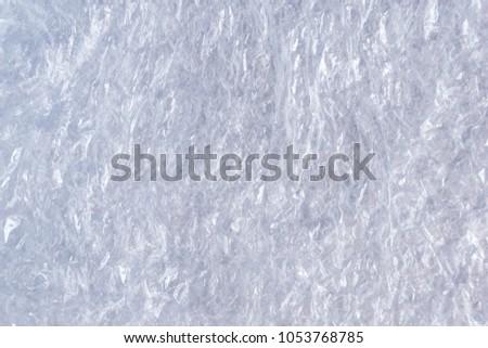 Crumpled polyethylene backdrop texture, flexible transparent plastic material #1053768785