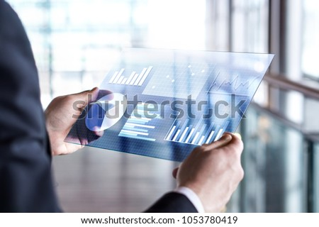 Transparent futuristic tablet. Business man using virtual touch screen. Modern mobile technology in accounting, finance, data and analytics. Internet of things (IOT) and augmented reality concept. Royalty-Free Stock Photo #1053780419