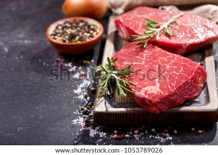 fresh meat with ingredients for cooking on dark table Royalty-Free Stock Photo #1053789026