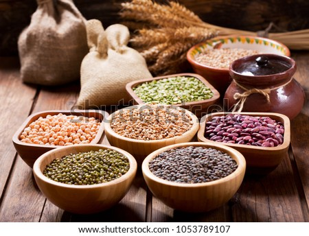 various cereals, seeds, beans and grains on wooden table Royalty-Free Stock Photo #1053789107