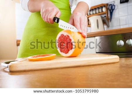 Woman's hands cutting fresh grapefruit on kitchen #1053795980