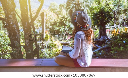 Asian woman travel nature. Travel relax. Study read a book. Nature Education Write a note At public park in summer. In Thailand #1053807869