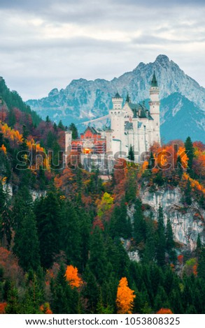 Scenic morning view on Neuschwanstein Castle with colorful autumn trees and the Alps on background. Bavaria, Germany. Beautiful autumn colorful scenery. #1053808325