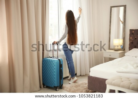 Young woman with luggage in hotel room #1053821183