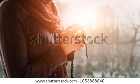 Christian Religion and hope concept. Woman hands praying with rosary and wooden cross. Bless god helping catholic on church background.