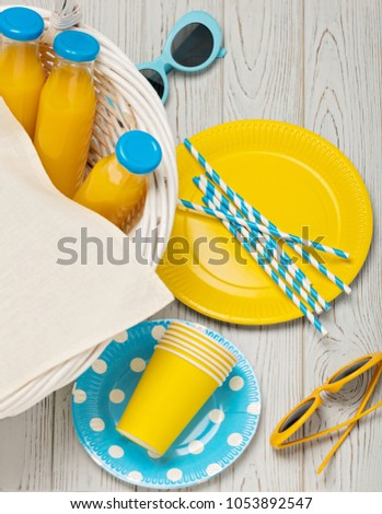 Summer picnic. Sweet picnic - orange juice and yellow and blue disposable dishes. Top view. #1053892547