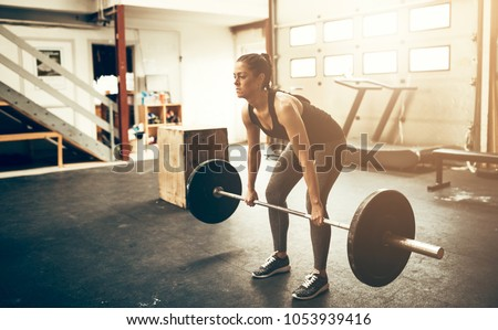 Focused young woman in sportswear lifting heavy weights while working out in a gym #1053939416