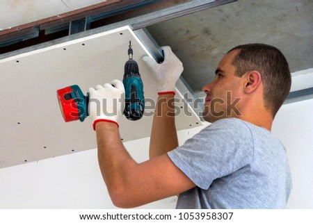 Construction worker assemble a suspended ceiling with drywall and fixing the drywall to the ceiling metal frame with screwdriver. Renovation, construction and do it yourself DIY concept. #1053958307