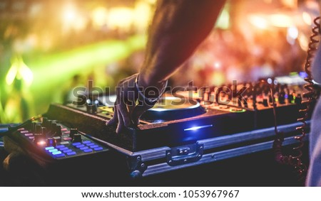Dj mixing outdoor at beach party festival with crowd of people in background - Summer nightlife view of disco club outside - Soft focus on hand fingers - Fun ,youth,entertainment and fest concept Royalty-Free Stock Photo #1053967967