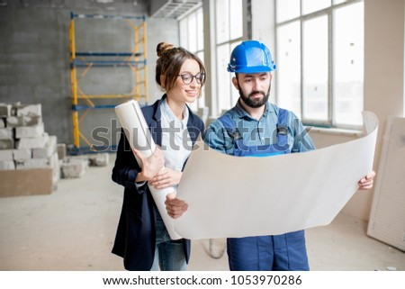 Foreman expertising the structure with businesswoman holding a blueprints at the construction site indoors #1053970286