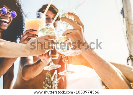 Group of happy friends cheering with tropical cocktails at boat party - Young people having fun in caribbean sea tour - Youth and summer vacation concept - Focus on bottom hands glass  #1053974366