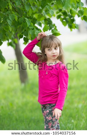 Little blond girl on background of green tree leaves. #1054037156