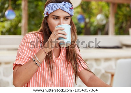 Thoughtful pleased female drinks coffee, being focused on something, wears striped casual shirt and headband, rests in outdoor coffee shop. Pleasant looking woman with hot aromatic beverage. #1054057364