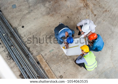 Top view of engineering team, site manager, field engineer and foreman working at constructed construction site. Business Concept for team work of heavy industry. #1054063535