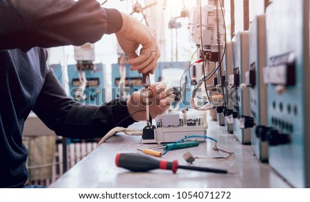 Electrician worker checking electricity meters. Electrical equipment. Background #1054071272