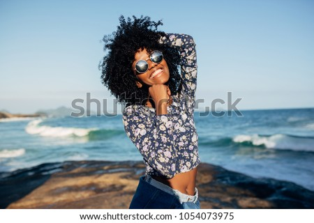 Young beautiful Brazilian girl staying on beach in Rio de Janeiro on warm sunny with embankment and tall residential houses in blurred background and laughing #1054073975