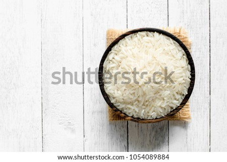 Rice in a wooden bowl is placed on a wooden floor. #1054089884