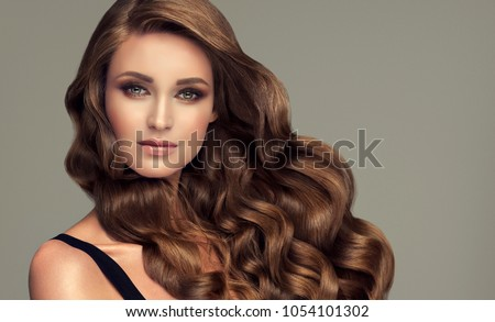 Brunette brown girl with long  and   shiny curly hair .  Beautiful  model woman  with curly hairstyle. Care , cosmetic and beauty  #1054101302