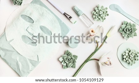 Skin care flat lay with facial sheet mask, mist spray bottle , succulents and orchid flowers on white desktop background, top view. Beauty spa and wellness concept Royalty-Free Stock Photo #1054109129