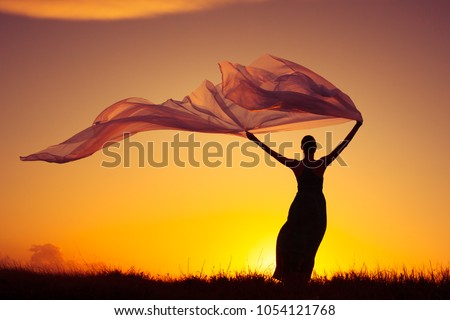 Woman outdoors in dress holding a long fabric blowing in the wind. Freedom and serenity concept.  Royalty-Free Stock Photo #1054121768