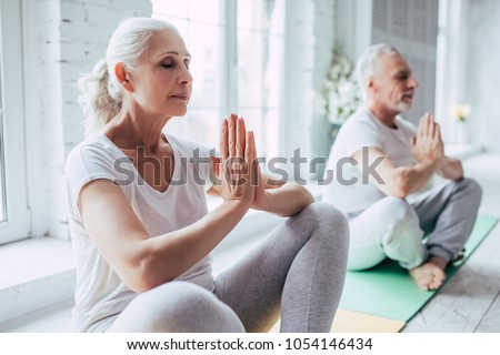 Senior couple is doing fitness training at home. Doing yoga together. Healthy lifestyle concept. #1054146434