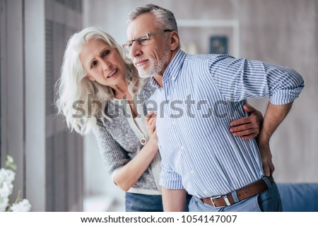 Senior couple at home. Handsome old man is having back pain and his attractive old woman supports him. #1054147007