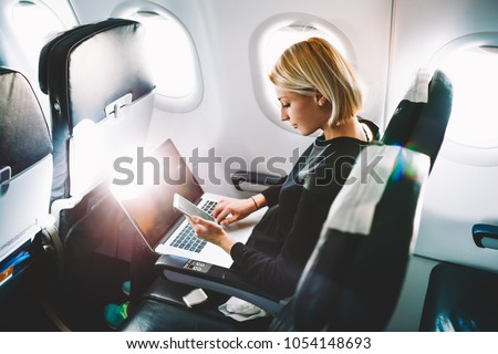 Blonde female tourist checking incoming notification on smartphone sitting on seat of airplane with netbook.Young businesswoman share media from telephone on laptop computer during plane flight #1054148693