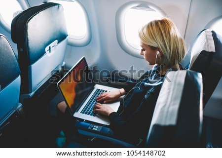 Attractive caucasian female passenger of airplane sitting in comfortable seat listening music in earphones while working at modern laptop computer with mock up area using wireless connection on board #1054148702
