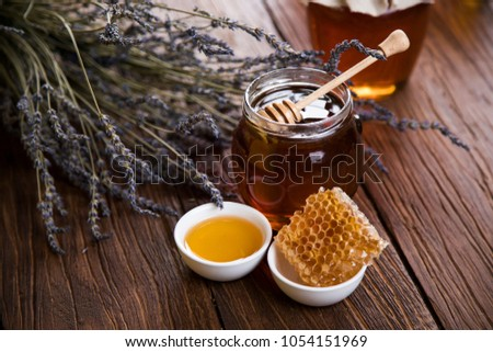 Honey dripping from a wooden honey dipper in a jar on wooden background #1054151969