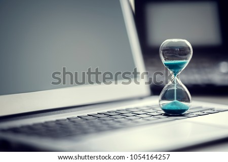 Hourglass on laptop computer concept for time management and countdown to deadline #1054164257