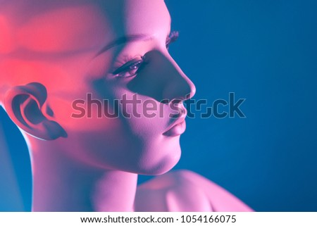 The face of the dummy. Female mannequin. Pink on the face. Female mannequin on a blue background. #1054166075