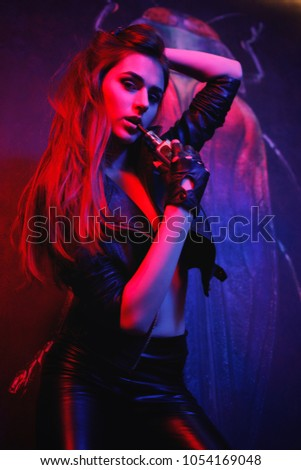 Young sexy woman is vaping ( smoking ) e-cigarette. Brutal sexy girl in black jacket and leather pant. Sexy rock star girl smoke electric cigarette in leather jacket, leather leggings and high heels. #1054169048