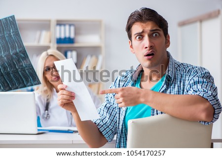 Male patient angry at expensive healthcare bill Royalty-Free Stock Photo #1054170257