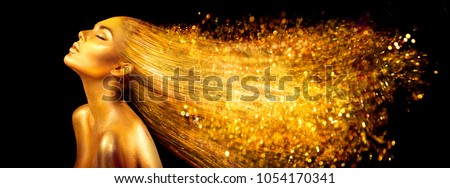 High Fashion model woman in golden bright sparkles. Art Gold skin girl face portrait closeup. Beauty gold eyes, Lips, Skin and  dyed hair. Lady with holiday Glamour shiny professional makeup on black #1054170341